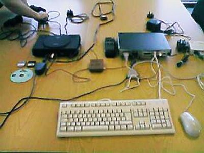 A black Playstation and a Netstation with lots of wires, a keyboard and a mouse