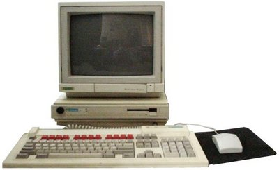 "A310 system - monitor sitting on a flat base unit, with a matching keyboard and mouse.  The base unit has a 3.5"" floppy drive in one side."