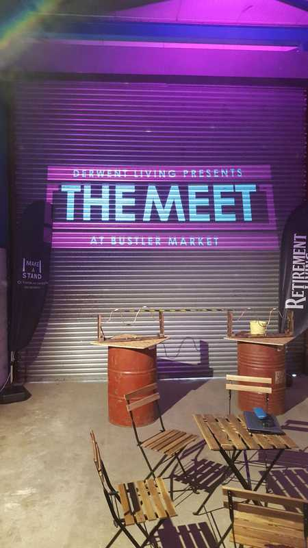 The Meet logo projected on a shutter; there are banners to the sides and rustic furniture in front.