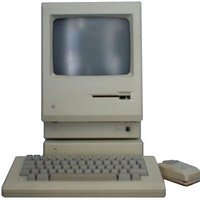 Probably an original Apple Macintosh.  Flat base unit, monitor with floppy drive under the screen, chunky keyboard and mouse.